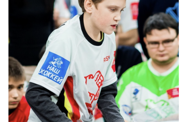 Photograph of a boy playing Stiga Table Hockey with Crowd Background.
